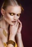 Mujer hermosa en accesorios con las hojas del oro Imagenes de archivo