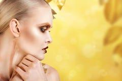 Mujer hermosa en accesorios con las hojas del oro Fotografía de archivo libre de regalías