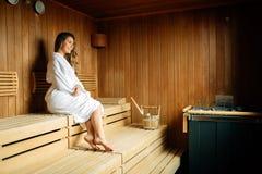 Mujer hermosa en aceites de colada de la sauna en piedras calientes fotografía de archivo libre de regalías