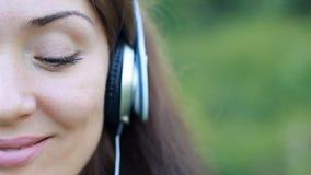 Mujer hermosa en auriculares que escucha la música Medio primer de la cara El humor, placer, relajación, se relaja metrajes