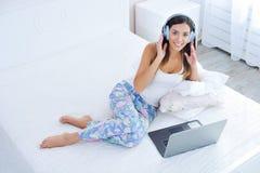 Mujer hermosa en auriculares y con el ordenador portátil en cama Fotos de archivo libres de regalías