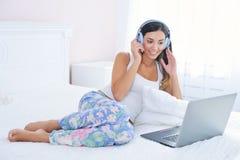 Mujer hermosa en auriculares y con el ordenador portátil que estudia en cama Imagenes de archivo