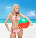 Mujer hermosa en bikini con la pelota de playa Imagenes de archivo