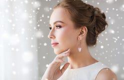 Mujer hermosa en blanco con el pendiente de la perla Foto de archivo libre de regalías