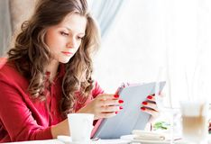 Mujer hermosa en café de la ciudad Ella café de consumición de la identificación y usar su tableta Foto de archivo