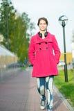 Mujer hermosa en calle del otoño de la capa que camina roja Imágenes de archivo libres de regalías
