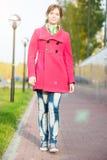 Mujer hermosa en calle del otoño de la capa que camina roja Fotos de archivo