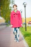 Mujer hermosa en calle del otoño de la capa que camina roja Imagen de archivo libre de regalías