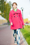 Mujer hermosa en calle del otoño de la capa que camina roja Imagenes de archivo