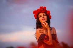 Mujer hermosa en campo de la amapola en la puesta del sol foto de archivo