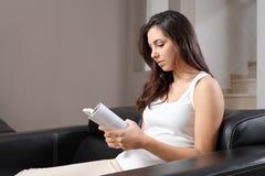 Mujer hermosa en casa que se sienta en un sofá que lee un libro Fotografía de archivo libre de regalías