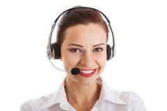 Mujer hermosa en centro de atención telefónica con el micrófono y los auriculares. Fotos de archivo