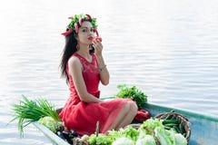 Mujer hermosa en el barco con las verduras Imagen de archivo