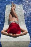 Mujer hermosa en el bikiní taning en la piscina Imagen de archivo libre de regalías