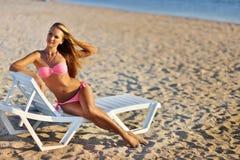 Mujer hermosa en el bikini atractivo que se relaja en la playa del verano Fotos de archivo libres de regalías