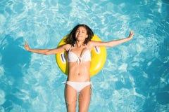 Mujer hermosa en el bikini blanco que flota en el tubo inflable en piscina Imagenes de archivo