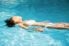 Mujer hermosa en el bikini blanco que flota en piscina Fotos de archivo libres de regalías
