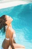 Mujer hermosa en el bikini blanco que se sienta por el lado de la piscina Foto de archivo