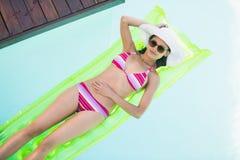 Mujer hermosa en el bikini que miente en cama de aire en piscina Foto de archivo libre de regalías