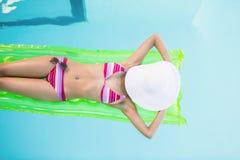 Mujer hermosa en el bikini que miente en cama de aire en piscina Fotografía de archivo libre de regalías