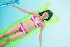 Mujer hermosa en el bikini que miente en cama de aire en piscina Imágenes de archivo libres de regalías