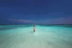Mujer hermosa en el bikini que salpica el agua en el mar Imágenes de archivo libres de regalías