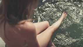 Mujer hermosa en el bikini que se sienta en el embarcadero de madera que disfruta de tiempo por un lago almacen de metraje de vídeo