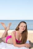 Mujer hermosa en el bikini rosado que miente en la playa Fotos de archivo