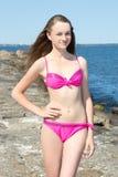 Mujer hermosa en el bikini rosado que presenta en la playa rocosa Imagen de archivo libre de regalías