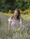 Mujer hermosa en el día soleado que lleva el vestido rosado y que se sienta en el campo fresco del lavander, disfrutando de la be Imagen de archivo