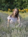 Mujer hermosa en el día soleado que lleva el vestido rosado y que se sienta en el campo fresco del lavander, disfrutando de la be Fotografía de archivo