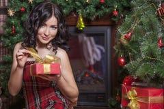 Mujer hermosa en el estilo del Año Nuevo con un regalo en manos Foto de archivo libre de regalías