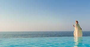 Mujer hermosa en el estilo griego en piscina del infinito Foto de archivo libre de regalías