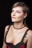 Mujer hermosa en el negro que mira para arriba Imagenes de archivo