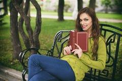 Mujer hermosa en el parque que lee un libro en un banco Imagenes de archivo