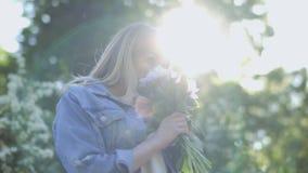 Mujer hermosa en el ramo del olor de la chaqueta del dril de algodón de peonías metrajes