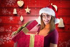 Mujer hermosa en el sombrero de santa que abre una caja de regalo Fotografía de archivo