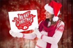 Mujer hermosa en el sombrero de santa que lleva a cabo el cartel de la Navidad Imágenes de archivo libres de regalías