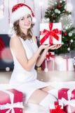 Mujer hermosa en el sombrero de santa que se sienta cerca de la Navidad adornada tr Imágenes de archivo libres de regalías