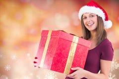 Mujer hermosa en el sombrero de santa que sostiene el regalo de la Navidad Foto de archivo