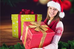 Mujer hermosa en el sombrero de santa que sostiene los regalos de la Navidad Foto de archivo libre de regalías