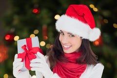 Mujer hermosa en el sombrero de santa que sostiene un regalo de la Navidad Imágenes de archivo libres de regalías