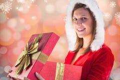 Mujer hermosa en el sombrero de santa que sostiene un regalo de la Navidad Fotos de archivo libres de regalías