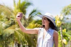 Mujer hermosa en el sombrero que hace el retrato de la foto de Selfie sobre la muchacha tropical de Forest Landscape Happy Smilin Foto de archivo libre de regalías