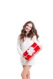 Mujer hermosa en el suéter blanco que sostiene una caja roja con un regalo Fotos de archivo