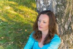 Mujer hermosa en el suéter que descansa al lado del árbol y del thinkin Imágenes de archivo libres de regalías