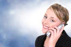 Mujer hermosa en el teléfono sin cuerda de la casa contra fondo azul Fotos de archivo libres de regalías
