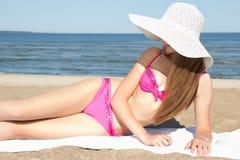 Mujer hermosa en el traje de baño rosado que miente en la playa Imagenes de archivo