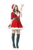 Mujer hermosa en el traje de Santa Claus que sostiene el cepillo rosado del plumero que sonríe en la cámara Imagen de archivo