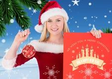 Mujer hermosa en el traje de santa que sostiene la tarjeta y la chuchería de la Feliz Navidad Imágenes de archivo libres de regalías